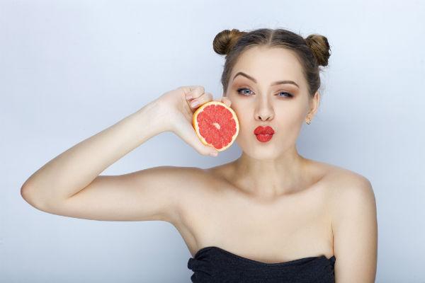 בחורה צעירה מחזיקה תפוז אדום