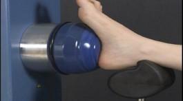 כף רגל נחה על משענת שחורה ומוצמדת לרכיב עגול של מכשיר הארטרוסקופ שמיועד לטיפול בגלי הלם