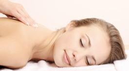 אישה שוכבת על מיטת טיפולים במהלך העיסוי הרפואי אותו מקבלת